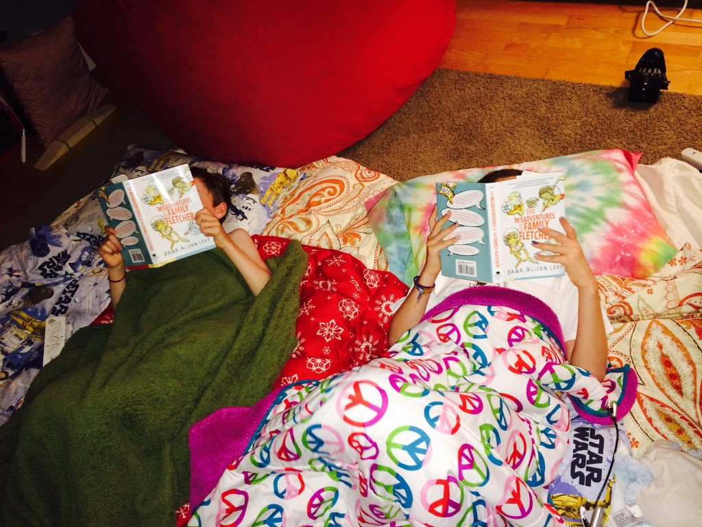 Two readers back at home, camped out with their new books