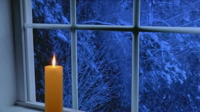 stock-footage-golden-candle-glows-in-front-of-window-with-heavy-snow-storm-seen-outside-at-night